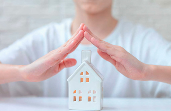 hands protecting house to symbolize insurance services